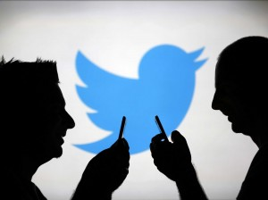 twitter logo with two people facing each other and holding mobile devices
